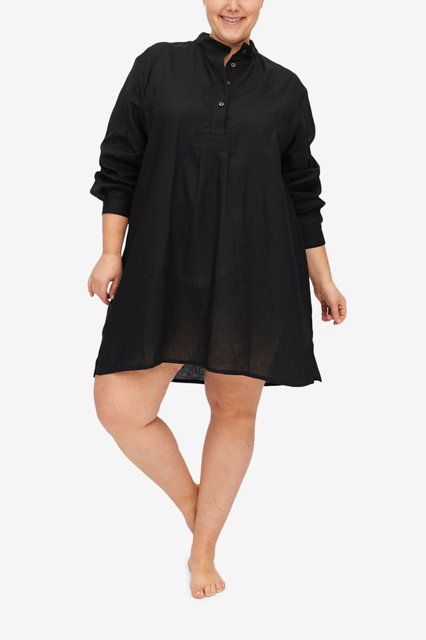 Charlotte looks cute while balancing on one foot with her legs crossed at the ankles. The black linen short sleep shirt hangs beautifully and looks luxurious.