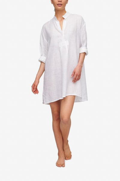 Front view of the White Linen Short Sleep Shirt, its full length sleeves are folded up to the elbow. The placket has 2 or 3 buttons open for an effortless look.