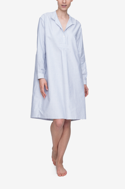 Emily wears the below the knee length, long version of our classic nightshirt. Shown here in Blue Oxford Stripe, it has long sleeves and a stand collar with a couple buttons open and the stand collar folded down flat.