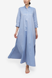 A full length chemise in a medium blue oxford cotton fabric. This nightshirt has a stand collar, a three quarterplacket and sleeves. Side slits make this piece move beautifully while prioritizing comfort.