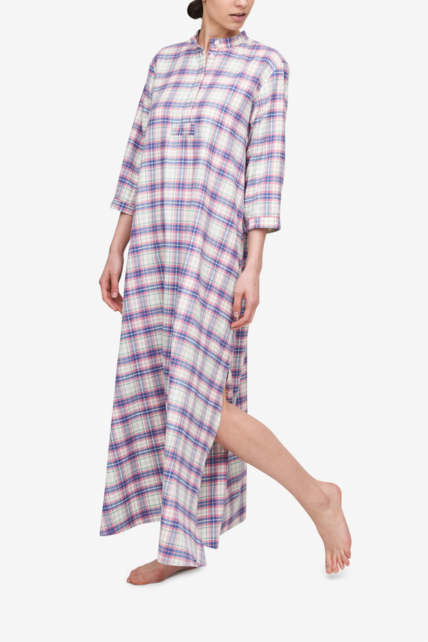 Woman wearing a full length flannel nightshirt with a pink check pattern