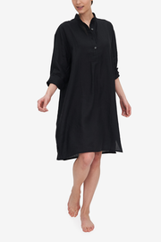 A woman takes a step and the nightshirt she is wearing moves around her. The Black linen looks both crisp and soft all at once. The Sleeves are rolled up to three-quarter length.