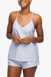 Cropped shot of a black woman, her torso is the focus. Wearing a spaghetti strap, v-neck camisole in Blue Oxford Stripe cotton.