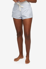 "A black woman is cropped at the waist, her bare legs and feet are seen. She is wearing a pair of pyjama shorts with a 2"" inseam. Made in a blue and white cotton shirting with an elastic waist band back and twill tape drawstring front."