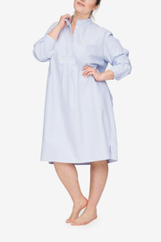 Front view of the Plus version of our classic long nightshirt. Shown here in Blue Oxford Stripe, the model is holding the collar away from her body to show off the three quarter placket.