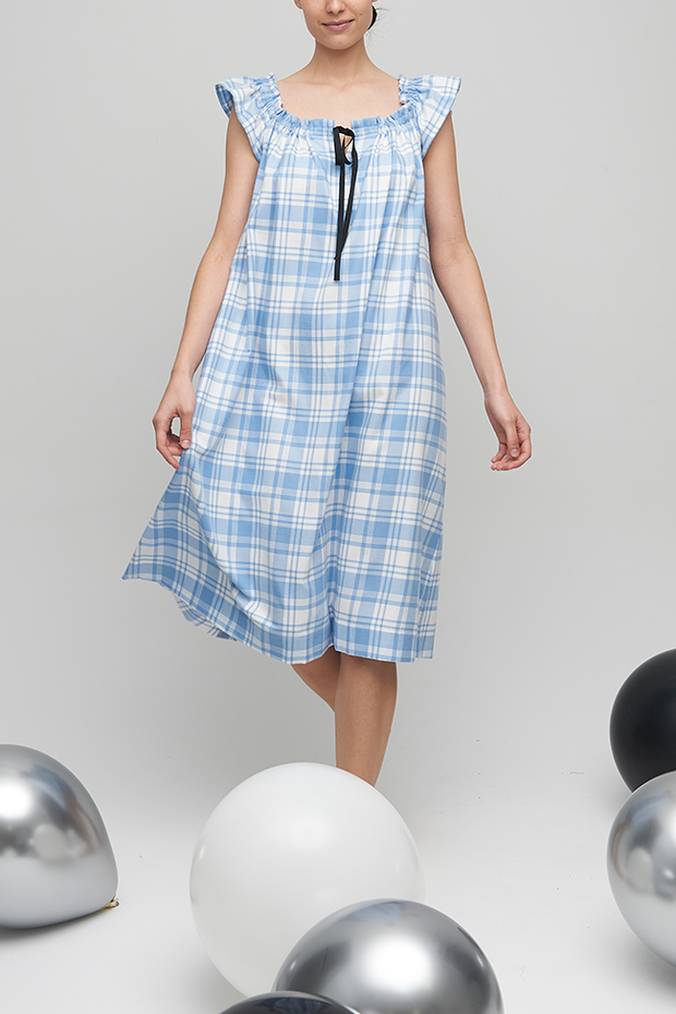 A slightly below the knee length nightdress in a super soft blue and white plaid flannel. It has black grosgrain ribbon around the neckline that can be gathered as much or as little as you like.