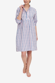 A woman grabs the collar of her Long Sleep Shirt to show the placket and collar details. It's made from a custom pink and blue geometric stripe, printed on a lightweight, white cotton shirting.