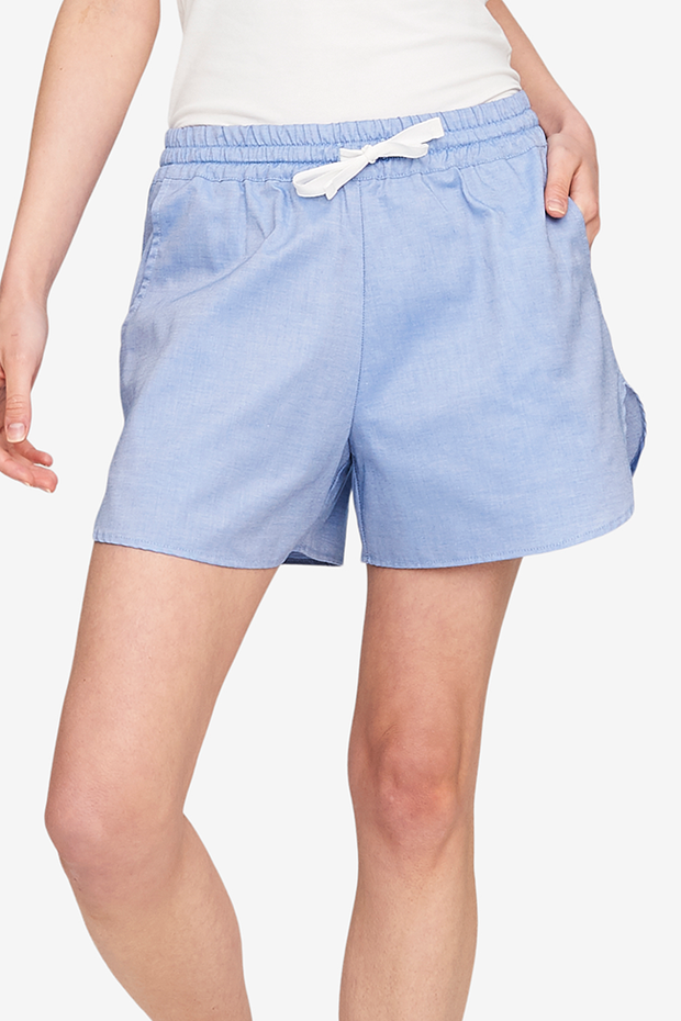 A close up shot of a pair of blue cotton shorts. They have an elastic waistband and a drawstring to make sure they fit just right. And pockets!