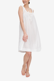 Emily is wearing the Sleeveless Nightie, a knee-length nightgown with a gathered neckline with the bow tied at centre front. It's made in our airy, sheer white Milano cotton and linen blend.