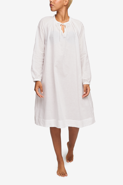 Full shot of a black woman with a blonde buzz cut. She's looking over her right shoulder as she walks toward the camera. Wearing a knee-length nightgown with raglan sleeves with button cuffs. There is a little bow at the centre front of the gathered neck line. Made in a ultra lightweight, sheer white cotton linen blend.