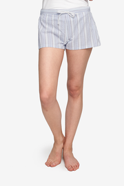 "A white woman is cropped at the waist, her bare legs and feet are seen. She is wearing a pair of pyjama shorts with a 2"" inseam. Made in a white cotton seersucker with vertical blue stripes.The shorts have an elastic waistband at the back and twill tape drawstring front."