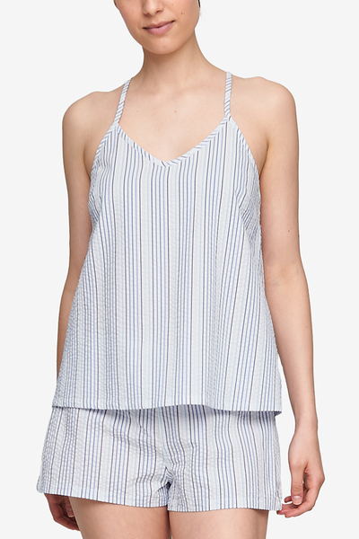Cropped shot of a white woman, her torso is the focus. Wearing a spaghetti strap, v-neck camisole in a white seersucker cotton with thin, vertical blue stripes..