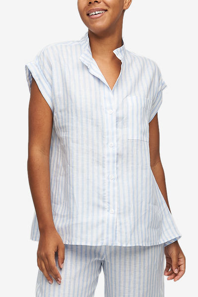 "Cropped shot of a black woman, her torso is the focus. Wearing a pyjama top with a full placket and cuffed, cap sleeves. One breast pocket on the left side. It's made from a crisp linen with 3/4"" blue and white stripes."