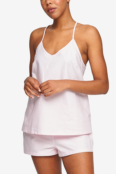 Cropped shot of a black woman, her torso is the focus. Wearing a spaghetti strap, v-neck camisole in Pink Oxford Stripe cotton.