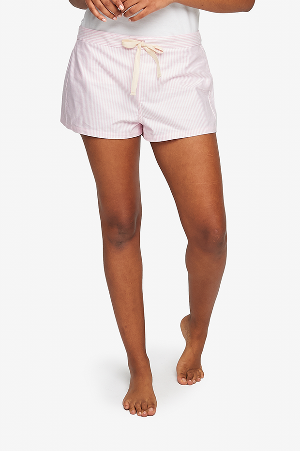 "A black woman is cropped at the waist, her bare legs and feet are seen. She is wearing a pair of pyjama shorts with a 2"" inseam. Made in a striped white and pink woven cotton. The shorts have an elastic waistband at the back and twill tape drawstring front."