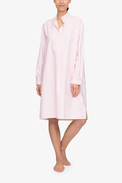 Emily wears the below the knee length, long version of our classic nightshirt. Shown here in Pink Oxford Stripe, it has long sleeves and a stand collar with a couple buttons open on the three quarter placket.