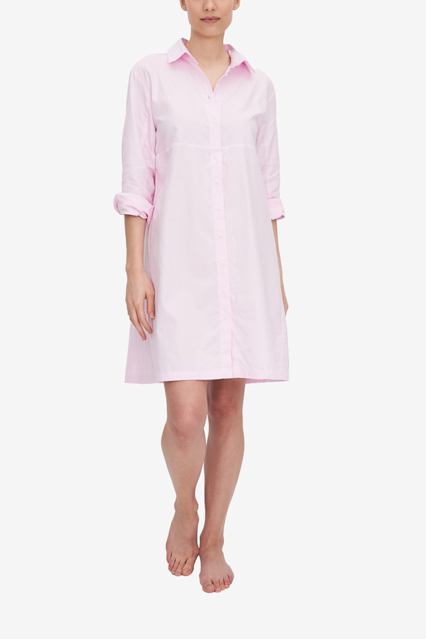 A woman wears a knee-length Sleep Shirt with a full length placket. It has seam under the bust line, a classic point collar and full length sleeve, rolled up to the elbow. The light pink Royal Oxford fabric hangs beautifully, showing off the A-Line silhouette nicely.
