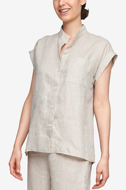 Cropped shot of a white woman, her torso is the focus. Wearing a pyjama top with a full placket and cuffed, cap sleeves. One breast pocket on the left side. It's made from a crisp linen in a cool, sandy beige colour.
