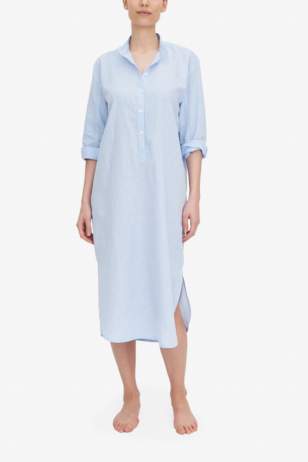 A woman wears a midi-length Sleep Shirt with a curved hem, stand collar and three-quarter placket. It's made from a light blue cotton and linen blend fabric.