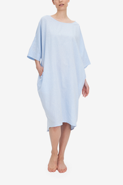 Emily wears our Pocket Kaftan in a gorgeous light blue linen and cotton blend fabric. The model has her hand in the pocket, and the cocoon silhouette can be seen .