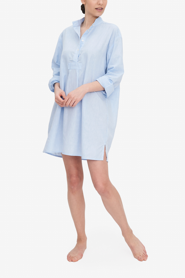 Emily wears our Short Sleep Shirt - a traditional, oversized shirt - made from a light blue linen and cotton blend fabric.