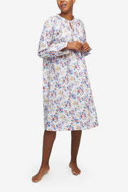 A black woman with a blonde buzz cut. She's looking over her right shoulder as she walks toward the camera. Wearing a knee-length nightgown with raglan sleeves with button cuffs. There is a little bow at the centre front of the gathered neck line. Made in a light cotton shirting with a nostalgic red, blue and yellow floral print.