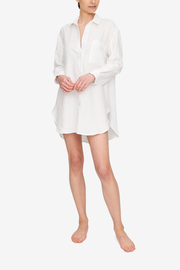 Full body shot of a women wearing a classic button up shirt made from pure white linen. It has long sleeves and comes down to mid thigh with a slightly shorter length in the front.