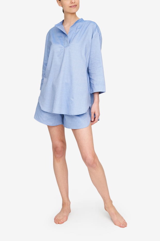 A full body shot of a woman who is wearing a blue pyjama set. Blue cotton three quarter sleeve top and matching shorts.