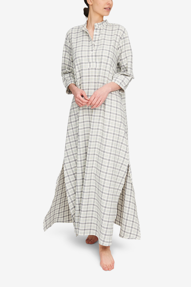 A woman wearing a full length Sleep Shirt. It's a super soft, lightweight, cream and grey plaid flannel.