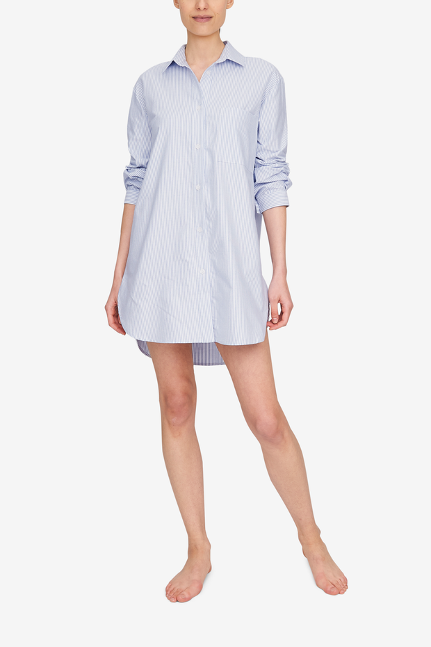 Full body shot of a woman wearing a shirt that comes down to mid-thigh, long sleeves, a pointed collar. Made out of a beautiful blue and white striped cotton oxford shirting.
