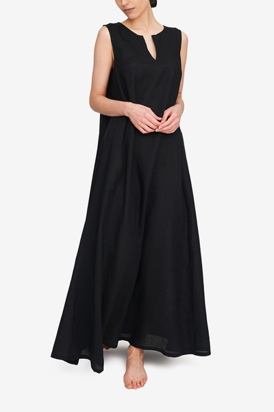 Front view of the sleeveless, floor length day dress in our best selling black linen. Split neckline makes it feminine, the exaggerated a-line silhouette gives ease of movement and drama.