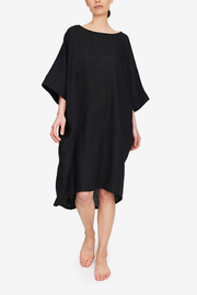 Full body shot of the Pocket Kaftan in our favourite - black linen. A wide boat neck, big, wide elbow length sleeves and a cocoon silhouette. A slight high-low hem makes this piece modern and easy to wear.