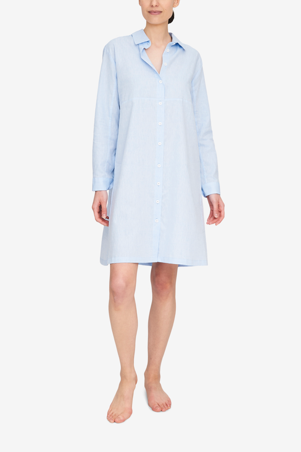 A woman wears the Button Down Sleep Shirt, with a full length placket. It hits at about the knee, and can be worn for sleep as well as a day dress. The light blue linen cotton blend fabric is timeless and chic.