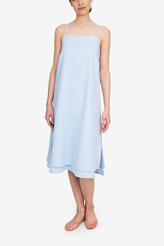Front view of the Two Layer Dress, shown here in a light blue cotton and linen blend. The dress has a square neckline, spaghetti straps that cross in the back and a double layer body with different hem lengths - the outer layer is a couple inches shorter. Side slits make this shape sway and move when being worn.