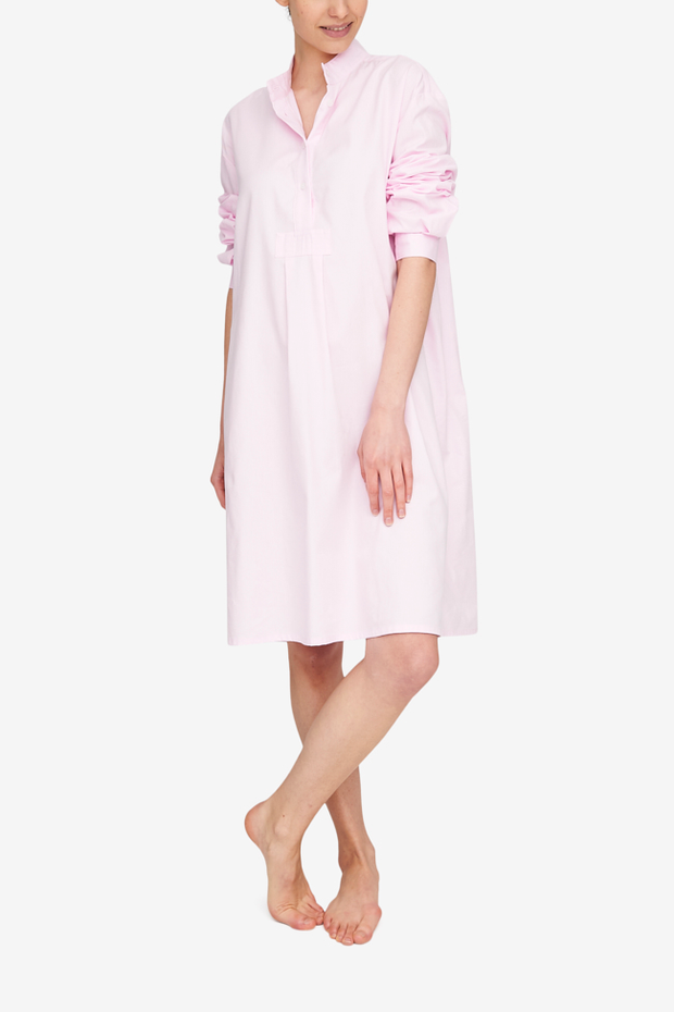 A textured Royal Oxford Cotton in a light pink colour shown in our Long Sleep Shirt shape. The wearer stands with her ankles crosse and arms hanging loosely at her sides. The full length sleeve are pushed up to her elbows.