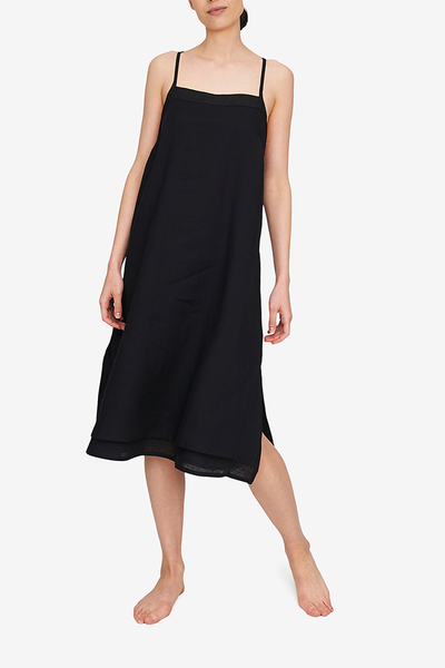 Front view of the Two Layer Dress, shown here in black linen. The dress has a square neckline, spaghetti straps that cross in the back and a double layer body with different hem length - the outer layer is a coupe inches shorter. Side slits make this shape sway and move when being worn.