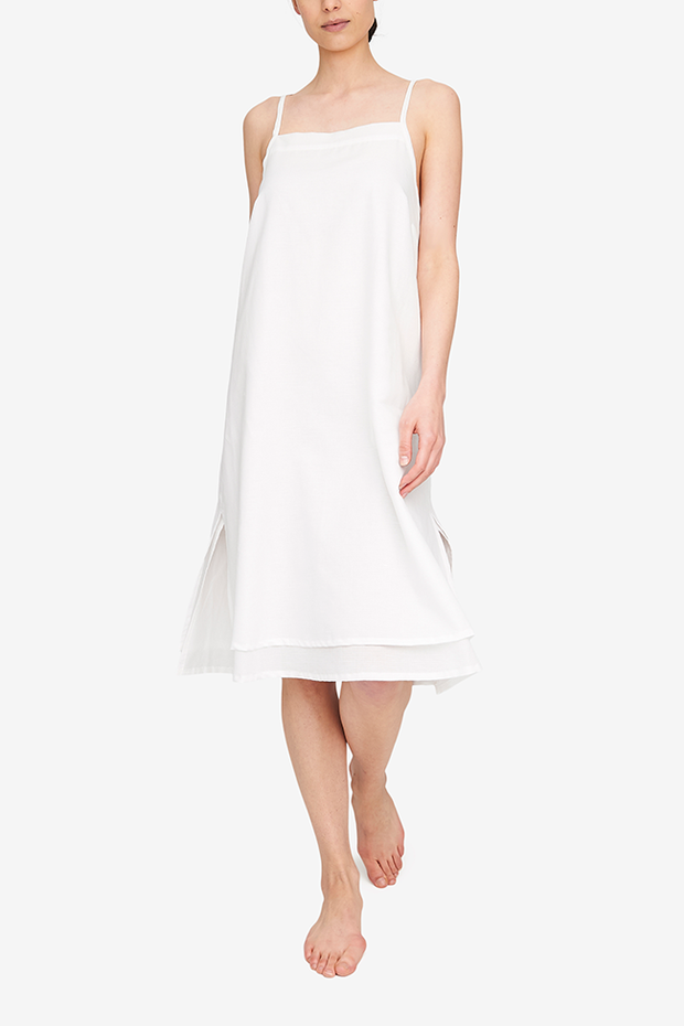 Front view of the Two Layer Dress, shown here in our lightweight, white Milano cotton/linen blend. The dress has a square neckline, spaghetti straps that cross in the back and a double layer body with different hem lengths - the outer layer is a couple inches shorter. Side slits make this shape sway and move when being worn.