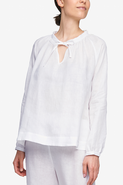 Cropped shot of a white woman, her torso is the focus. She is wearing a pyjama top with raglan sleeves with button cuffs, the hem hitting her at the hip. There is a little bow at the centre front of the gathered neck line. Made in our favourite, crisp white linen.