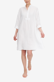 Emily walks towards the camera, making the white linen of the Long Sleep Shirt she is wearing swing. The full length sleeves are rolled up and the collar us undone, she looks confident and relaxed.