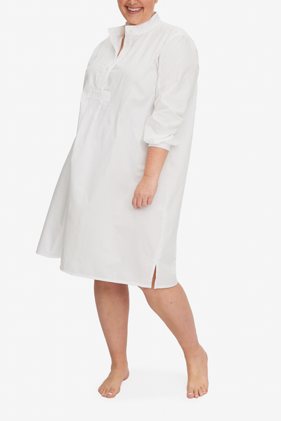 A smiling woman wears a Long Sleep Shirt in white royal oxford cotton. Simple and easy to wear, this falls below the knee on most and offers modesty as well as  comfort.