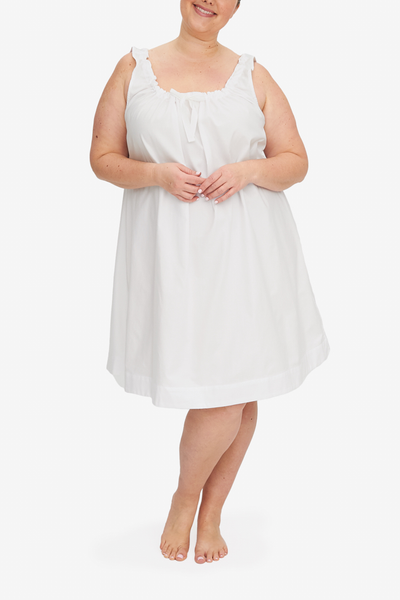 Front view of the Sleeveless Nightie Plus, it's knee length and has a unique gathered necking with the bow tied at centre front. Shown here in a classic white royal oxford shirting, a fabric with great texture and drape.