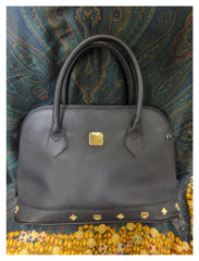 Vintage MCM black bolide style bag with gold tone metal studded charms. Rare masterpiece purse for unisex use. Phenomenon