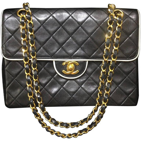 Vintage Chanel black lambskin 2.55 classic shoulder bag with gold chain and cc closure. Unique white edge design.