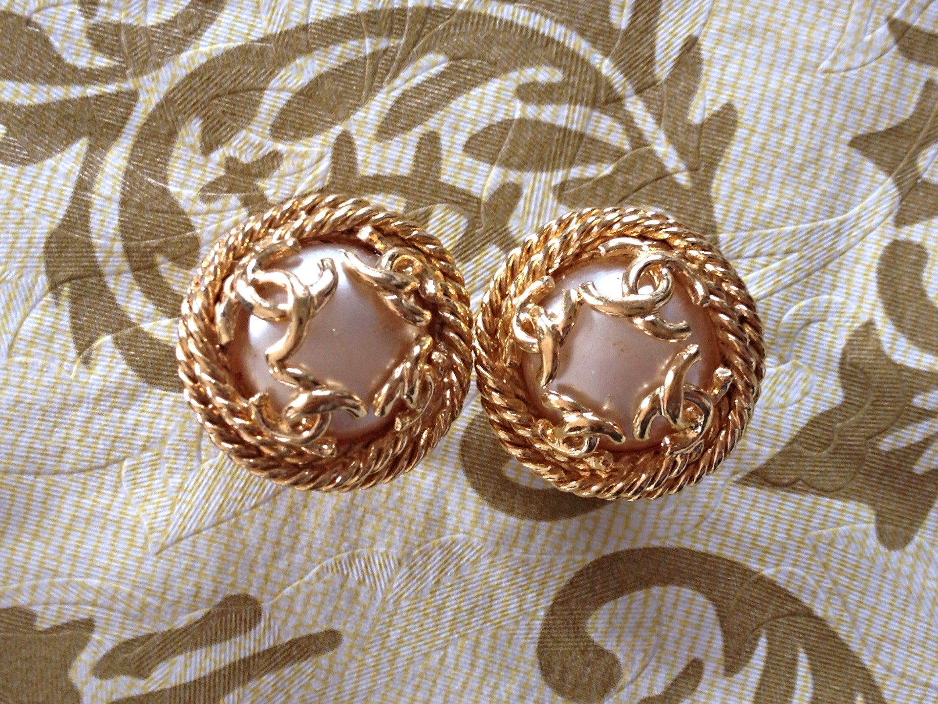 Vintage CHANEL gold tone round earrings with twisted frames, a faux pearl and CC motifs. Great and rare Chanel vintage jewelry gift.