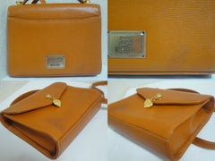 Vintage MOSCHINO orange brown leather kelly handbag with a detachable shoulder strap and golden heart shape logo charm.