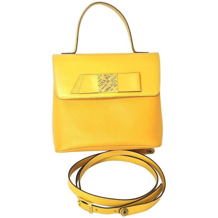 MINT. Vintage Nina Ricci yellow leather handbag purse with shoulder strap and golden logo embossed bow motif. Perfect summer bag.