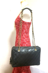 Vintage CHANEL black goatskin shoulder bag with stiches, gold tone chains, and large golden CC charm.