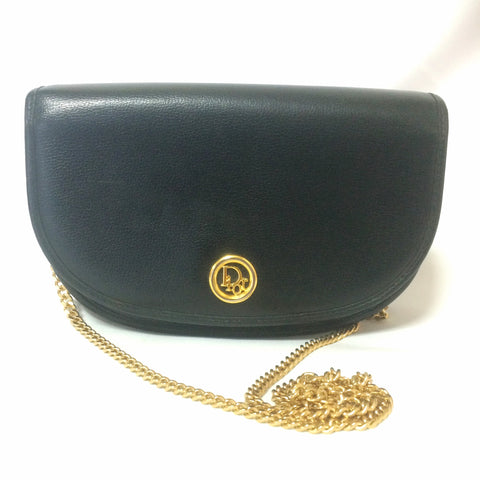 Vintage Christian Dior black leather halfmoon shape clutch purse, mini bag, with golden round logo motif and chain strap.