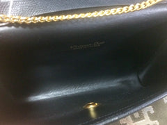 Vintage Christian Dior black leather clutch purse, mini bag, with golden Dior motif and gold tone chains.