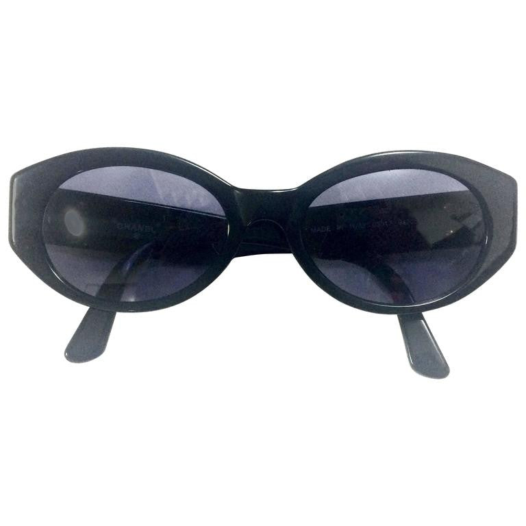 Vintage CHANEL black oval frame sunglasses with golden CC motifs at sides. Mod and chic eyewear you must get.